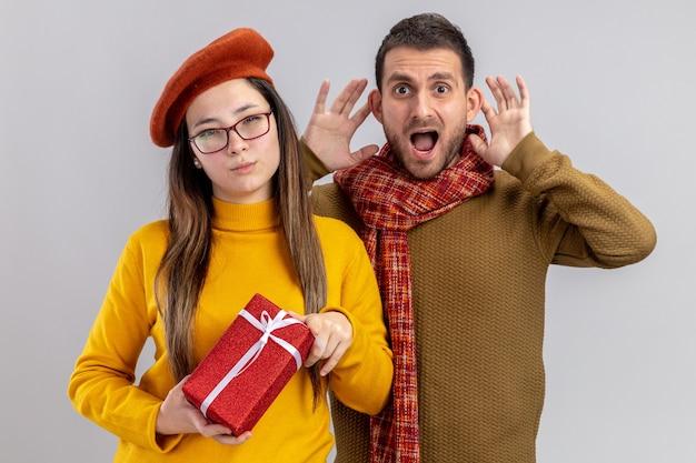 Młoda piękna para podekscytowany mężczyzna i uśmiechnięta kobieta w berecie trzymająca prezent z uśmiechem na twarzy świętuje walentynki stojąc nad białą ścianą