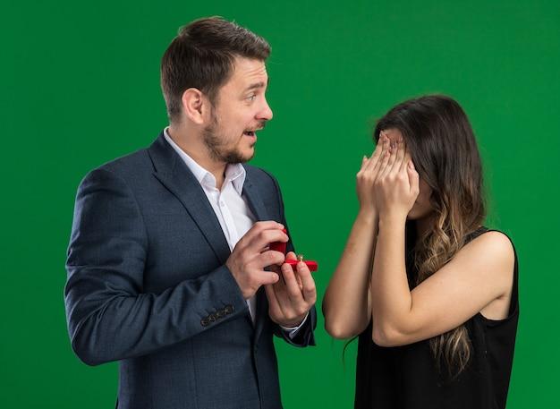 Młoda piękna para przystojny mężczyzna zamierza złożyć propozycję swojej uroczej podekscytowanej dziewczynie z zamkniętymi oczami świętującej walentynki stojącej nad zieloną ścianą