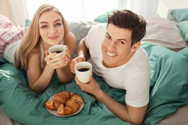 Młoda piękna para śniadanie na łóżku