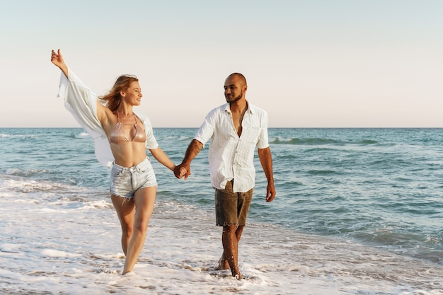 Młoda piękna para spaceru na plaży w pobliżu morza?