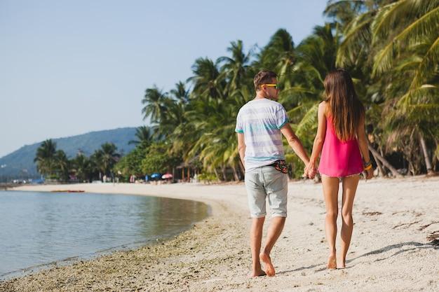 Młoda piękna para spacerująca po tropikalnej plaży, tajlandia, trzymanie się za ręce, widok z tyłu, strój hipster, styl casual, miodowy księżyc, wakacje, lato, romantyczny nastrój, zbliżenie nóg, szczegóły