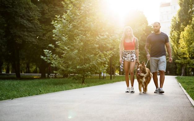 Młoda piękna para spacerująca z psem w letnim parku