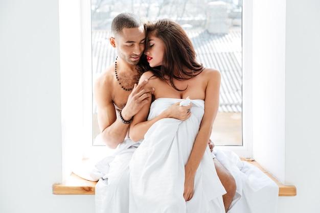 Młoda piękna para stojąca razem i przytulająca się przy oknie