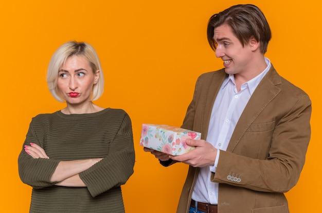 Młoda piękna para szczęśliwy człowiek daje prezent swojej niezadowolonej obrażonej dziewczynie