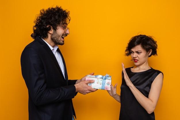 Młoda piękna para szczęśliwy mężczyzna daje prezent swojej odmawiającej niezadowolonej dziewczynie świętującej walentynki