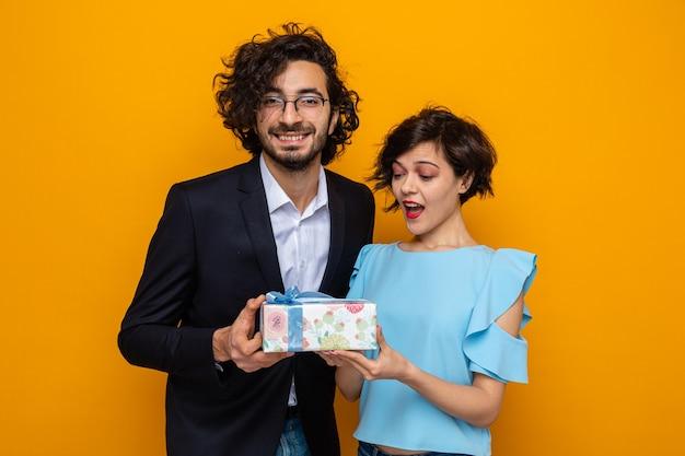 Młoda piękna para szczęśliwy mężczyzna daje prezent swojej zdziwionej i zdumionej dziewczynie świętującej walentynki