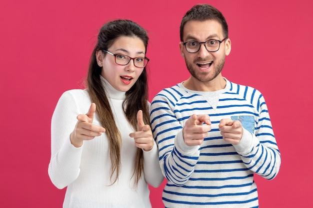 Młoda piękna para szczęśliwy mężczyzna i kobieta w ubranie w okularach szczęśliwy i wesoły, wskazując palcami wskazującymi