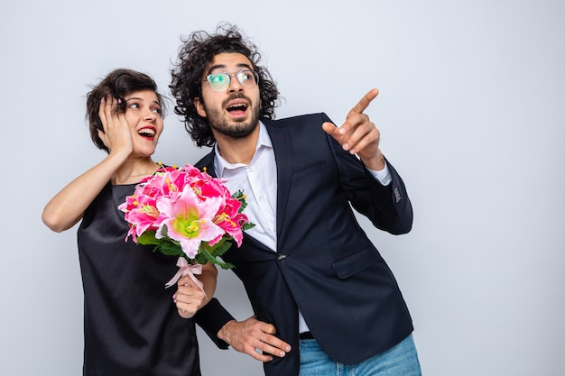 Młoda piękna para szczęśliwy mężczyzna i kobieta z bukietem kwiatów patrząc na bok szczęśliwi i zaskoczeni, wskazując palcami wskazującymi na bok, świętując międzynarodowy dzień kobiet 8 marca