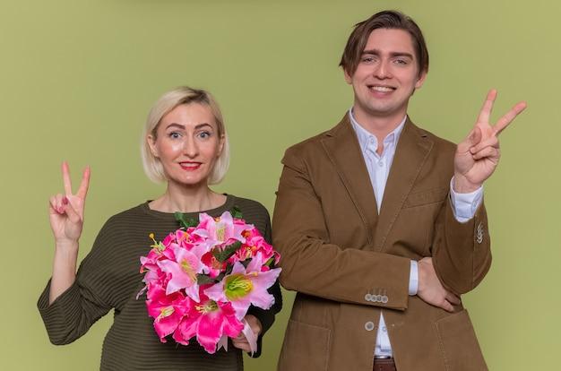 Młoda piękna para szczęśliwy mężczyzna i kobieta z bukietem kwiatów patrząc z przodu, uśmiechając się wesoło, pokazując znak v świętujący międzynarodowy dzień kobiet stojący nad zieloną ścianą