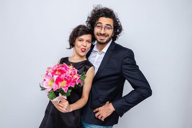 Młoda piękna para szczęśliwy mężczyzna i kobieta z bukietem kwiatów patrzący uśmiechnięci radośnie bawiący się razem