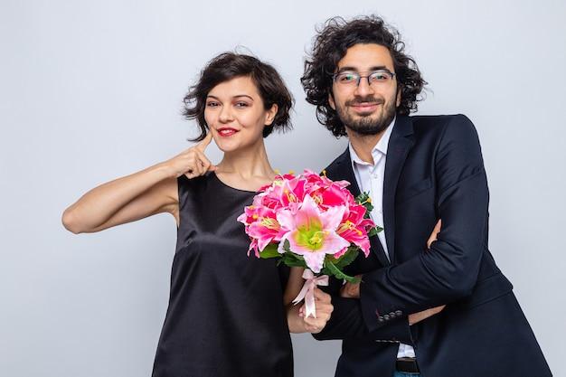 Młoda piękna para szczęśliwy mężczyzna i kobieta z bukietem kwiatów szczęśliwi w miłości uśmiechający się radośnie świętując międzynarodowy dzień kobiet 8 marca stojąc na białym tle