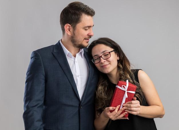 Młoda piękna para szczęśliwy mężczyzna i kobieta z prezentem szczęśliwi w miłości razem świętują walentynki stojąc na białej ścianie