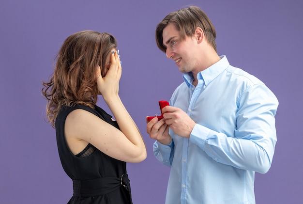 Młoda piękna para szczęśliwy mężczyzna składa propozycję z pierścionkiem zaręczynowym w czerwonym pudełku dla swojej uroczej dziewczyny, która zakrywa oczy rękami podczas walentynek stojąc na niebieskim tle