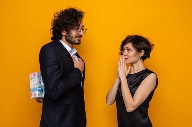 Młoda piękna para szczęśliwy mężczyzna ukrywa prezent przed swoją zaskoczoną i zdezorientowaną dziewczyną obchodzi międzynarodowy dzień kobiet 8 marca stojąc na pomarańczowym tle