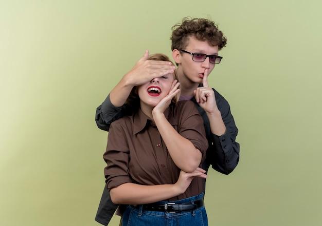 Młoda piękna para ubrana w ubranie szczęśliwy mężczyzna robi gest ciszy z palcem na ustach, zamykając oczy swojej dziewczyny, robiąc niespodziankę stojąc nad jasną ścianą