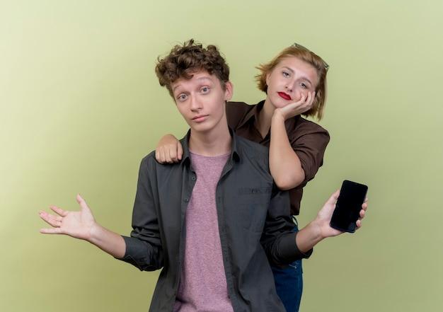 Młoda piękna para ubrana w zwykłe ubrania zdezorientowany mężczyzna trzymający smartfona wzruszający ramionami, a jego dziewczyna niezadowolona stojąc nad jasną ścianą