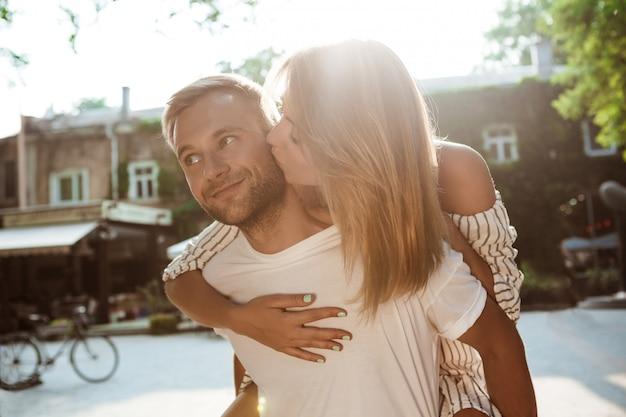 Młoda piękna para uśmiecha się, całuje, obejmuje, chodzi w parku.