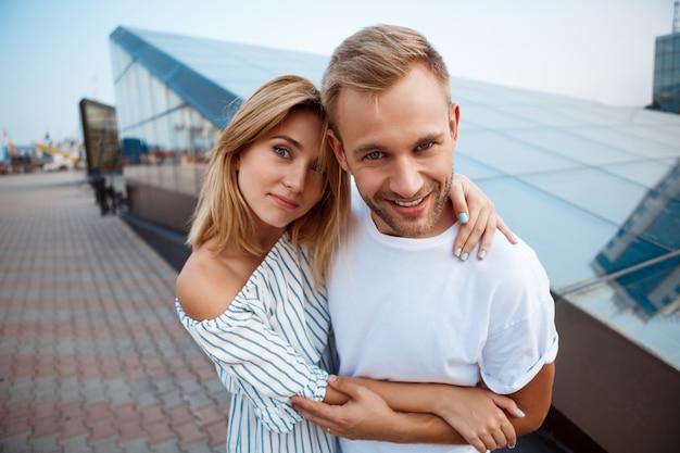 Młoda piękna para uśmiecha się, obejmując, spacerując po mieście.