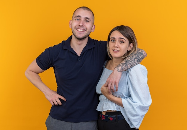 Młoda piękna para w codziennych ubraniach mężczyzna i kobieta szczęśliwi i pozytywnie spędzający czas razem uśmiechający się radośnie stojący