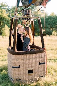 Młoda piękna para w czarnych ubraniach, całująca się w koszu balonu na ogrzane powietrze, ciesząca się swoim pierwszym lotem w ciepły letni wschód słońca na polu