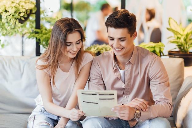Młoda piękna para w kawiarni! chłopiec i kobieta przeglądają menu na letnim tarasie