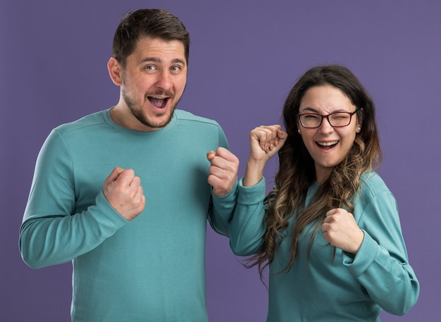 Młoda piękna para w niebieskich ciuchach mężczyzna i kobieta szczęśliwi i podekscytowani zaciskaniem pięści szczęśliwi w miłości stojącej nad fioletową ścianą