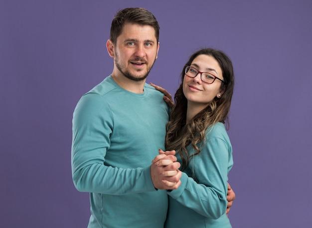 Młoda piękna para w niebieskich ciuchach szczęśliwa i wesoła uśmiechnięta kobieta i mężczyzna tańczą razem szczęśliwi w miłości stojąc nad fioletową ścianą