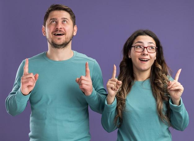 Młoda piękna para w niebieskich strojach casualowych mężczyzna i kobieta patrzący w górę uśmiechający się radośnie wskazujący palcami wskazującymi w górę stojący nad fioletową ścianą