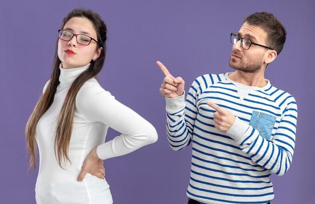Młoda piękna para w ubranie zdezorientowany mężczyzna wskazując palcem wskazującym na swoją poważną dziewczynę koncepcja walentynki stojącego na fioletowym tle