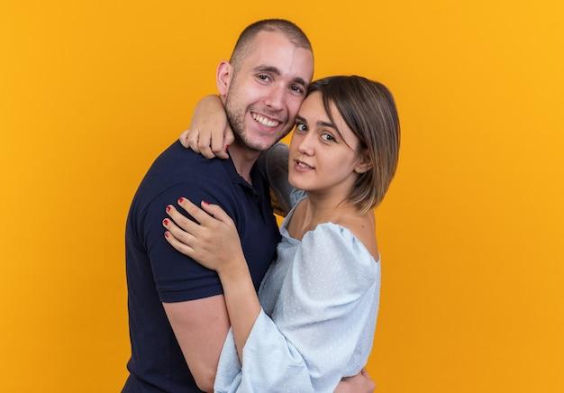 Młoda piękna para w zwykłych ubraniach mężczyzna i kobieta obejmując szczęśliwą w miłości uśmiechniętą patrząc stojącą