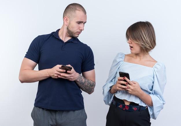 Młoda piękna para w zwykłych ubraniach mężczyzna i kobieta trzymający smartfony patrzący na siebie zdezorientowani stojąc nad białą ścianą