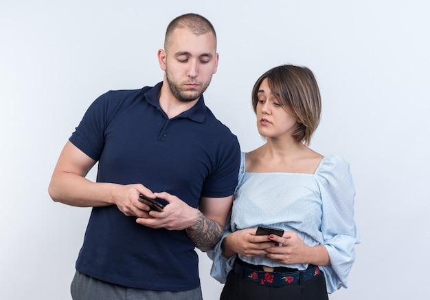 Młoda piękna para w zwykłych ubraniach mężczyzna i kobieta trzymający smartfony patrzący podejrzliwie stojący nad białą ścianą