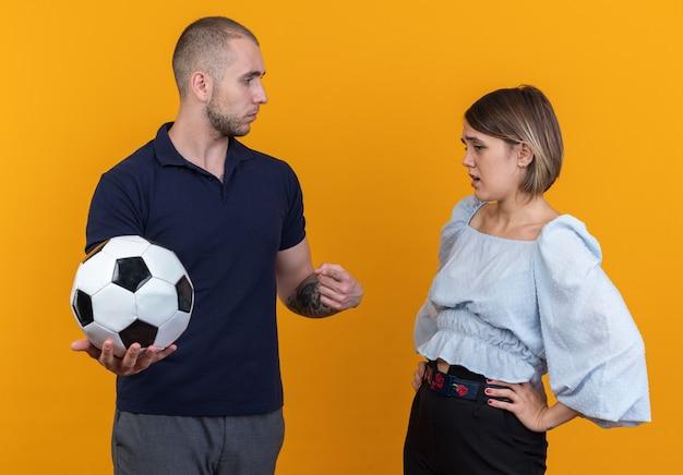 Młoda piękna para w zwykłych ubraniach mężczyzna z piłką nożną, patrząc na swoją zdezorientowaną i niezadowoloną dziewczynę stojącą
