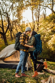 Młoda piękna para z plecakiem turystycznym całuje się w lesie w pobliżu namiotu