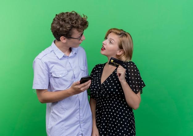 Młoda piękna para zaskoczony mężczyzna trzyma kartę kredytową holdiong i patrząc na swoją pewną siebie dziewczynę stojącą nad zieloną ścianą