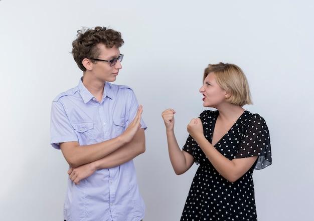 Młoda piękna para zły kobieta patrząc z zaciśniętymi pięściami na swojego zdezorientowanego chłopaka, który pokazuje gest stopu na białej ścianie