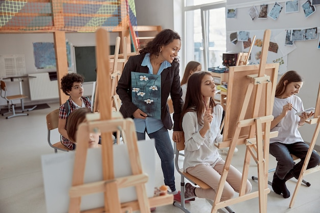 Młoda piękna, pewna siebie nauczycielka pomaga dziecku w lekcji grupowej w białej, nowoczesnej, minimalistycznej klasie