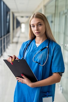 Młoda piękna pielęgniarka stoi na korytarzu ze stetoskopem i tabletem. koncepcja medycyny