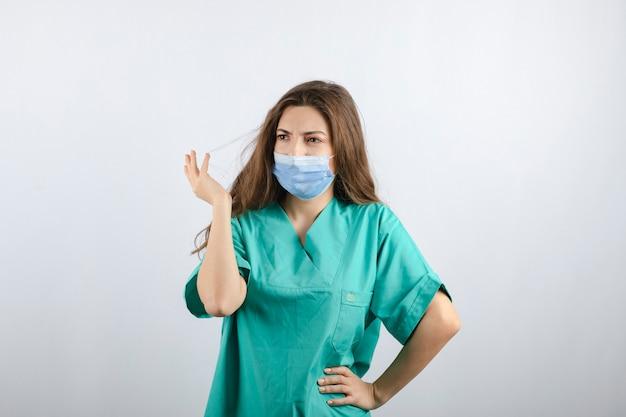Młoda piękna pielęgniarka w zielonym mundurze w masce medycznej