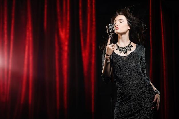 Młoda piękna piosenkarka w czarnej sukience z płynącymi włosami śpiewa do mikrofonu