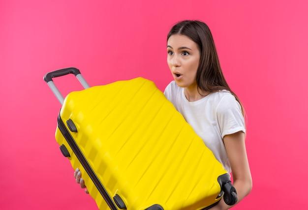 Młoda piękna podróżniczka dziewczyna trzyma walizkę patrząc na bok zaskoczony i zdezorientowany