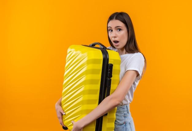 Młoda piękna podróżniczka dziewczyna trzyma walizkę patrząc zaskoczony i zdumiony