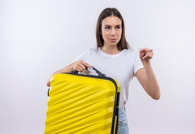 Młoda piękna podróżniczka dziewczyna trzyma walizkę, patrząc zaskoczony, wskazując palcem wskazującym na bok
