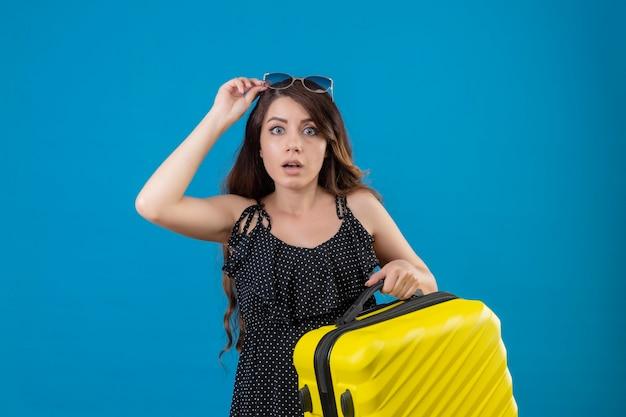 Młoda piękna podróżniczka dziewczyna w sukience w groszki trzyma walizkę patrząc zaskoczony i zdumiony patrząc na aparat stojący na niebieskim tle