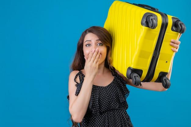 Młoda piękna podróżniczka dziewczyna w sukience w groszki trzyma walizkę patrząc zaskoczony, zakrywając usta ręką stojącą na niebieskim tle