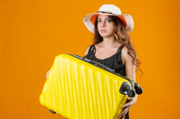 Młoda piękna podróżniczka dziewczyna w sukience w groszki w letnim kapeluszu trzyma walizkę patrząc niespokojną stojącą na żółtym tle