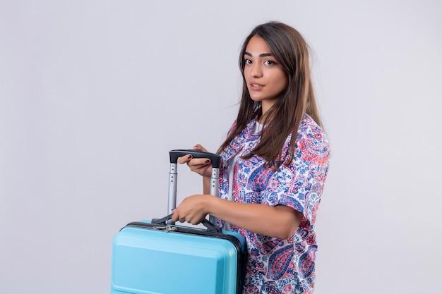Młoda piękna podróżniczka kobieta trzyma niebieską walizkę patrząc na bok z pewnym siebie wyrazem, gotowa do podróży po białej ścianie