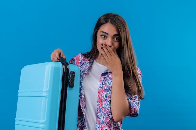 Młoda piękna podróżniczka kobieta trzyma niebieską walizkę patrząc zaskoczony i zdumiony, zakrywając usta ręką na niebieskiej ścianie