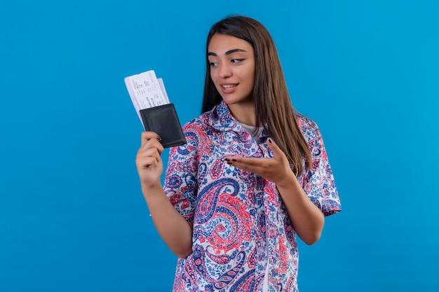 Młoda piękna podróżniczka kobieta trzyma paszport z biletami, wskazując ręką na nich, patrząc pozytywnie i szczęśliwie uśmiechając się stojąc na niebieskim tle