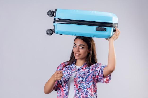 Młoda piękna podróżniczka kobieta trzyma walizkę na głowie z pewnym siebie wyrazem, wskazując palcem na aparat na białej ścianie